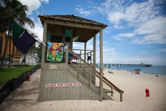 Lifeguard Station in Front of Pier. This is Deerfield Beach, Florida with a lifeguard station in the foreground that has a sign in red and white that says please stock photos