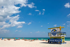 Lifeguard Station Miami Beach Florida. Tourists sunbath on Miami Beach, Florida, USA, next to a colorfully painted lifeguard station on February 15, 2017 Stock Images