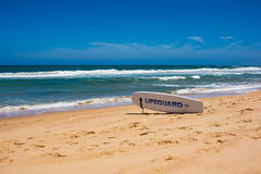 Lifeguard surfboard on ocean beach on sunny day Royalty Free Stock Photos