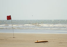 Lifeguard surfboard and red flag on the beach Stock Images