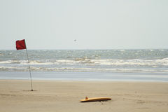 Lifeguard surfboard and red flag Stock Image