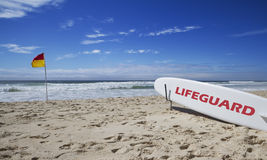 Lifeguard surfboard and safe flag at beach. Lifeguard surfboard on the beach near a safe swimming flag Royalty Free Stock Photo