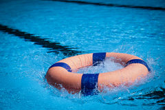 Lifeguard throw Life ring to save someone in swiming pool Stock Photos