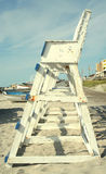 Lifeguard Tower. A bright daylight shot of the side of a row of blue and white painted wooden lifeguard chairs on a sandy beach, with a boardwalk, lifeboats, and Stock Photo