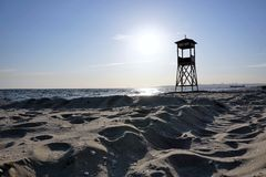 Lifeguard tower on beach at daytime with blue sky and wavy sea background. royalty free stock photography