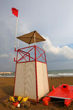 Lifeguard tower on the beach with the red flag fluttering in the Stock Photography