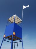 Lifeguard tower. Blue lifeguard tower with white flag over clear blue sky Royalty Free Stock Images