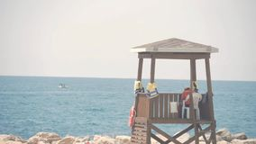 Lifeguard tower on a bright sunny summer day, with blue sky and sea in the background. Lifeguard tower on a bright sunny summer day, with blue sky and sea in stock footage