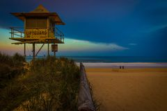 Lifeguard tower in grass near sand beach, sea and humans royalty free stock image