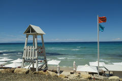 Lifeguard tower with lifeguard flag on a Greek beach. A lifeguard tower with a relevant flag saying lifeguard in Greek and English on a summer beach at royalty free stock images