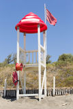 Lifeguard tower with red roof and flag at sandy beach Royalty Free Stock Images