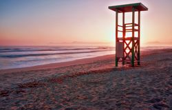 Lifeguard tower, sunrise, footprints on secluded beach with mountains and calm sea, playa de muro, alcudia, mallorca, spain stock image