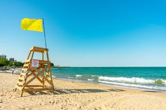 Lifeguard Tower with Yellow Flag on a Chicago Beach looking North. A lifeguard tower with a yellow flag on a Lake Michigan beach in Lincoln Park Chicago stock photo