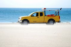Lifeguard Truck Sandblasted. Strong wind gusts sandblast this bright yellow Lifeguard truck on the beach Royalty Free Stock Photo
