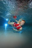 Lifeguard underwater in the pool. Lifeguard with red swimsuit and safety buoy underwater in the pool royalty free stock photo