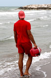 Lifeguard with uniform controls bathers with stormy sea. Lifeguard with red uniform controls bathers with stormy sea Royalty Free Stock Photo