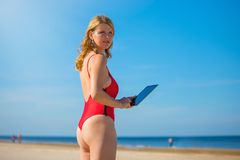 Lifeguard using tablet computer. On the beach royalty free stock photography