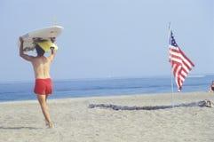 Lifeguard walking past an American flag Stock Image
