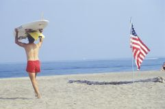 Lifeguard walking past an American flag planted in the sand, Lake Erie, Pennsylvania Royalty Free Stock Photography
