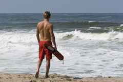 Lifeguard walking towards ocean Royalty Free Stock Image