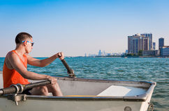 Lifeguard is Watching from the Boat. Lifeguard behind the paddles is watching at the beach in the big city Royalty Free Stock Photography