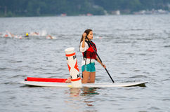 Lifeguard Watching. A volunteer lifeguard watches over competitors from a surfboard, during the 2014 Sprint Triathlon in Pewaukee, Wisconsin Stock Photo