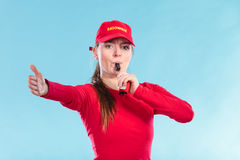 Lifeguard woman in cap on duty blowing whistle. Stock Image