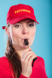 Lifeguard woman in cap on duty blowing whistle. Royalty Free Stock Image