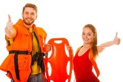 Lifeguards στη φανέλλα ζωής με το σημαντήρα διάσωσης επιτυχία Στοκ Εικόνες