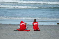 Lifeguards on the beach. 2 lifeguards looking out into the water, sitting on the sand royalty free stock photo