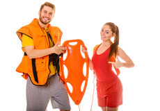 Lifeguards in life vest with rescue buoy. Lifeguards in life vest jacket pointing at rescue tube buoy . Man and women supervising swimming pool. Accident stock photos