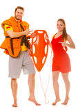 Lifeguards in life vest with rescue buoy. Lifeguards in life vest jacket pointing at rescue tube buoy . Man and women supervising swimming pool. Accident royalty free stock photo