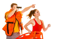 Lifeguards in life vest with rescue buoy running Royalty Free Stock Photo