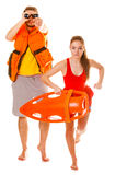 Lifeguards in life vest with rescue buoy running. Lifeguards with rescue tube buoy and life vest jacket looking through binoculars. Man and women supervising royalty free stock photography