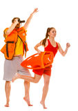 Lifeguards in life vest with rescue buoy running. Lifeguards with rescue tube buoy and life vest jacket looking through binoculars. Man and women supervising stock photography