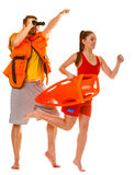 Lifeguards in life vest with rescue buoy running Royalty Free Stock Photos