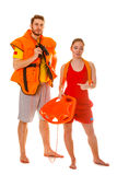 Lifeguards in life vest with rescue buoy. Lifeguards with rescue tube buoy and life vest jacket looking through binoculars. Man and women supervising swimming royalty free stock photography