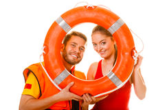 Lifeguards in life vest with ring buoy having fun. Happy lifeguards with ring buoy in life vest jacket. Man and women having fun. Accident prevention royalty free stock images