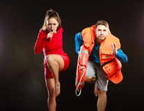 Lifeguards in life vest with ring buoy whistling. Stock Photography