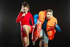 Lifeguards in life vest with ring buoy whistling. Lifeguards with rescue ring buoy lifebuoy and life vest jacket running to accident. Man and women supervising royalty free stock image