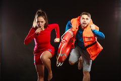 Lifeguards in life vest with ring buoy whistling. Stock Photo