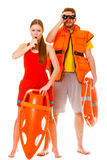 Lifeguards in life vest with ring buoy whistling. Lifeguards with rescue tube ring buoy lifebuoy and life vest jacket looking through binoculars. Man and women stock photos