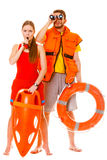 Lifeguards in life vest with ring buoy whistling. Royalty Free Stock Images