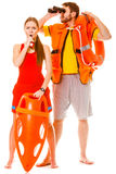 Lifeguards in life vest with ring buoy whistling. Lifeguards with rescue tube ring buoy lifebuoy and life vest jacket looking through binoculars. Man and women royalty free stock image