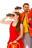 Lifeguards with rescue ring buoy and life vest. Lifeguards with rescue tube ring buoy lifebuoy and life vest jacket looking through binoculars. Man and women royalty free stock photo