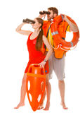 Lifeguards with rescue ring buoy and life vest. Lifeguards with rescue tube ring buoy lifebuoy and life vest jacket looking through binoculars. Man and women stock photography