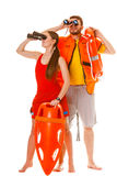 Lifeguards with rescue ring buoy and life vest. Lifeguards with rescue tube ring buoy lifebuoy and life vest jacket looking through binoculars. Man and women royalty free stock photos
