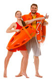 Lifeguards with rescue ring buoy and life vest. Lifeguards with rescue tube ring buoy lifebuoy and life vest jacket showing thumb up gesture. Man and women royalty free stock images