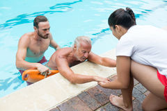 Lifeguards rescuing senior man from swimming pool Stock Photography