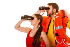 Lifeguards with ring buoy and life vest. Lifeguards with ring buoy lifebuoy and life vest jacket looking through binoculars. Man and women supervising swimming royalty free stock photos